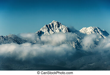 Mountain peak with snow in cloud on blue sky background, travel destination