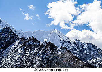 Mountain peaks in Himalayas Nepal. Beautiful nature mountains range landscape with snow and blue sky and clouds