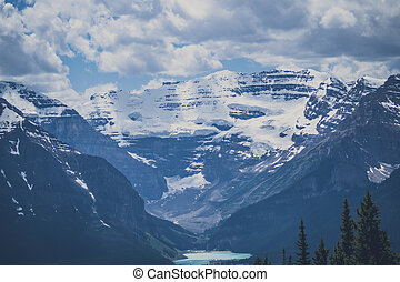 Mountain peaks with snow and cloudy sky
