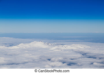 Mountain range emerging from endless white clouds, aerial shot.