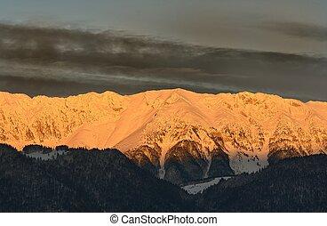 Mountain range lit by the rising sun. Piatra Craiului mountains.