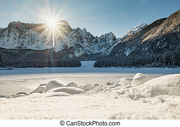 Mountain range Mangart seen from snow covert frozen lake...