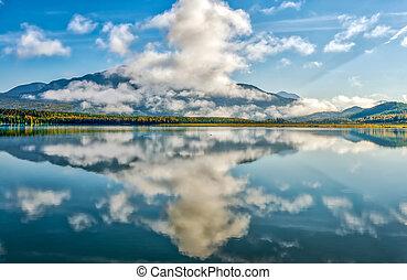 Mountain Reflections in a vivid blue glacial lake on the Alaskan Kenai Peninsula