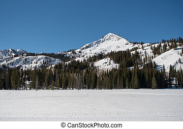 Mountain Ridge Above Snow Covered Lake