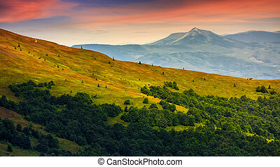 mountain ridge with peak behind the hillside at sunset -...