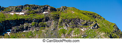 mountain ridge with rocky cliffs and grassy slopes....