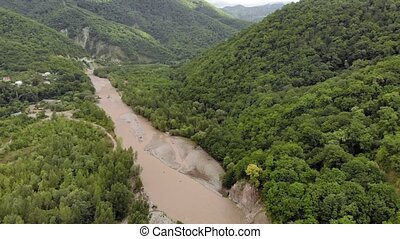 Mountain river. Aerial Video Filming - Flight over a muddy...