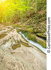 Mountain river flowing in the valley on a background of sunlight