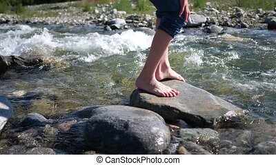 Mountain river. The guy is standing on a rock, the water...