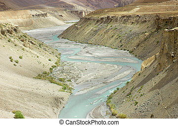 Mountain river with blue water between the hills.