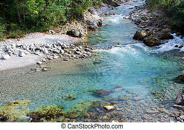 mountain river with clear tuquoise water and rocks
