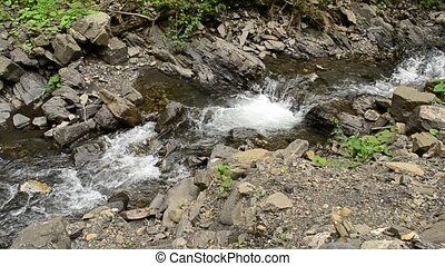 Mountain river with rapids, small waterfalls and foam
