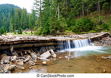 Mountain river with small waterfall