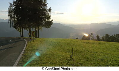 Mountain road in Alps, Austria. Panoramic view of mountains and green meadow