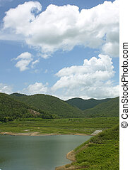 Natural forest landscape mountains sky water clouds.