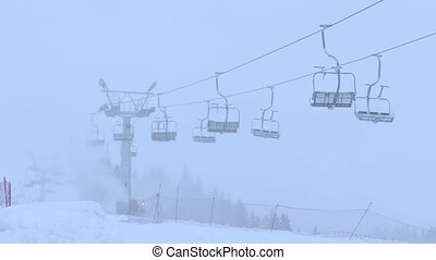 Mountain ski slope and operating empty chairlift in the fog...