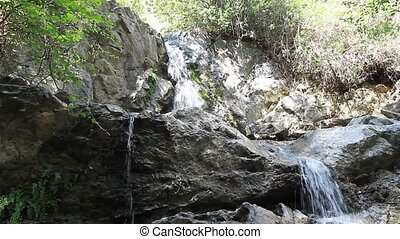 Mountain stone waterfall with crystal clear water
