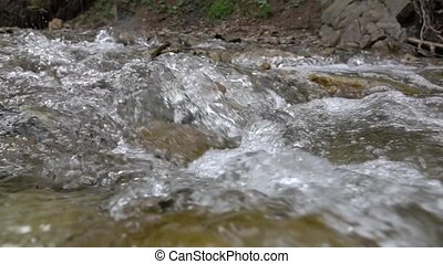 Mountain stream among stone banks with clear water. Slow motion