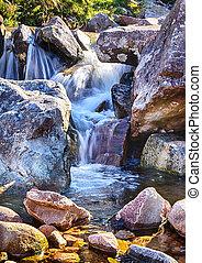 Mountain stream cascades over rocks - Smooth stream water ...