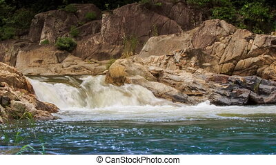 mountain stream flows among rocks falls into lake in park -...