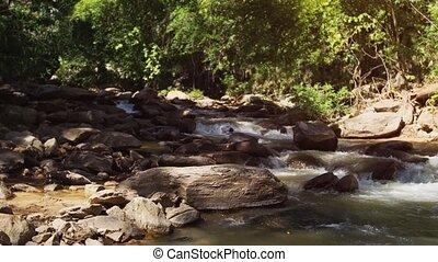 Natural, mountain stream hisses and burbles as it flows amongst rocks at Mae Ya Waterfall, near Chiang Mai, Thailand. Ultra HD 4k video