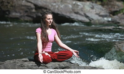 Mountain stream - Peaceful young woman sitting in lotus pose...