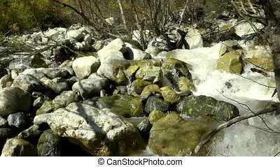 Natural mountain stream roars continuously as it tumbles and splashes over rocks and boulders in the Republic of Georgia. Ultra HD 4k stock footage with sound