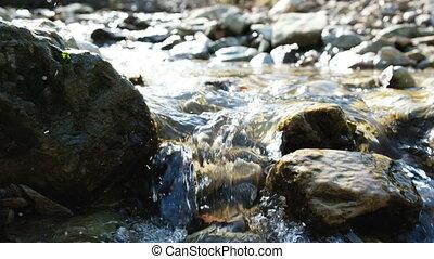 Mountain stream, water flows through the stones in spring, 4k.