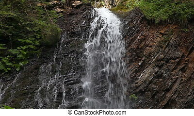 Mountain stream waterfall. The flow of net fast water falls...