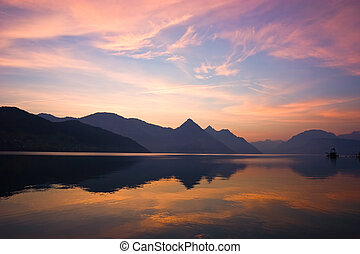 Beautiful sunrise over mountains, reflected on lake. Central Switzerland.
