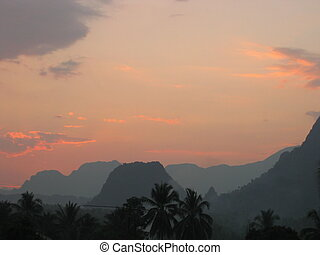 The sun setting behind the mountains. Vang Vieng. Laos
