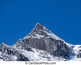 Mountain top with snow and clear blue sky