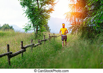Mountain trail in the meadow with man running with sticks in hand
