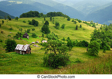green mountain valley and old wooden house