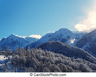Mountain valley with snow-capped peaks and forest against the blue sky. Ski resort