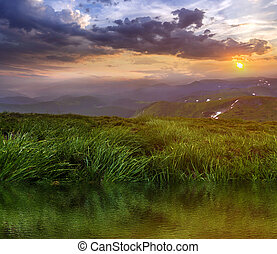 Mountain view at sunset or sunrise. Panorama of green grassy valley reflected in clear lake water, foggy mountains range with snow patches, dramatic cloudy sky and setting on horizon bright sun.