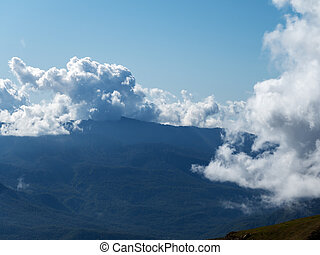 Mountain view with clouds lying on the mountains and clear blue sky