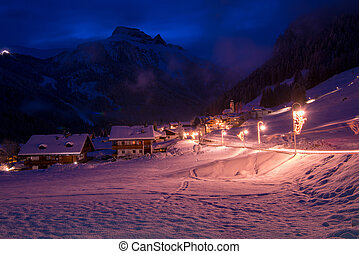 mountain village in alps at night in winte with fresh snow