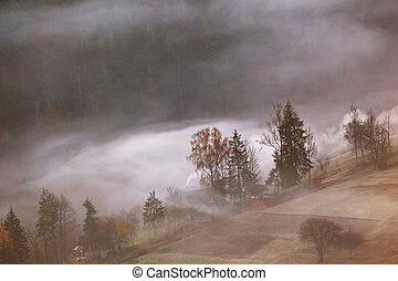 Mountain village in clouds of fog and smoke. autumn morning