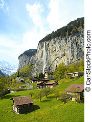 mountain village with church and waterfall, Alps, Switzerland .