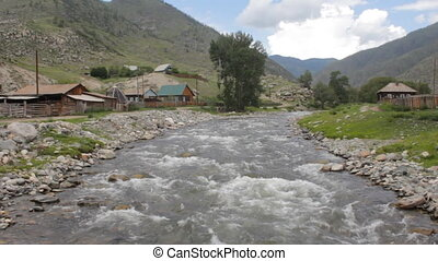 mountain village with rapids of river. mountain home beauty...