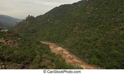 Mountain vista above a muddy river - High angle tilt down...
