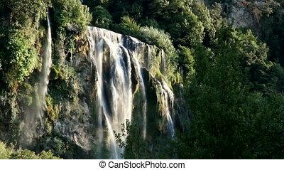 Mountain waterfall among greenery in the summer sun
