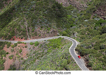 Mountain winding road with a red car