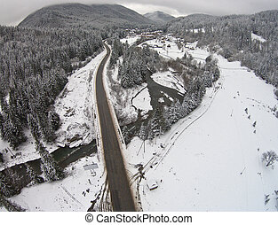 Mountain winter road that crosses the river
