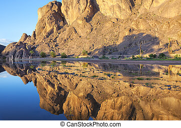Mountain with reflections in a river, Fint Oasis.