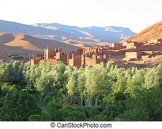 Mountain with sand dunes and a fortress in an oasis on the foreground - Gorges Dades valley - Morocco.