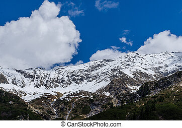 mountain with snow and clouds in sky
