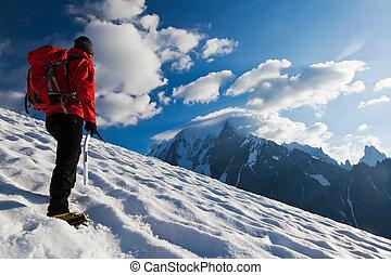 Mountaineer alone glacier - A male mountaineer walking...