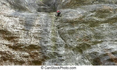 Mountaineer climbing up rock wall